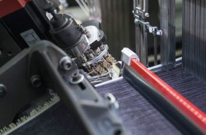 El iSAVER™ elimina el orillo de desperdicio en el lado izquerida de la tela para ofrecer ahorro de costos y tejido sostenible.